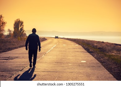A man walking on the concrete road along the sea at golden sunset