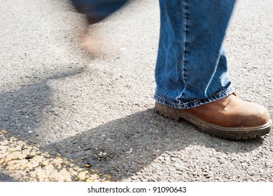 A man walking on concrete with work boots on.