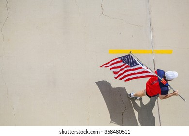 Man walking on cracked cement, carrying an American flag, view from above, focus on hat.