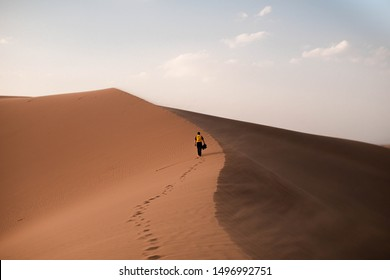 Man walking on a dune in Bafq desert, Iran
