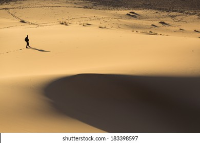 Man walking on dunes in desert