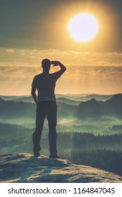 Man walking on the edge of a cliff high above misty valley.  Travel hiking and Lifestyle. Personal success concept, adventure active vacations outdoor