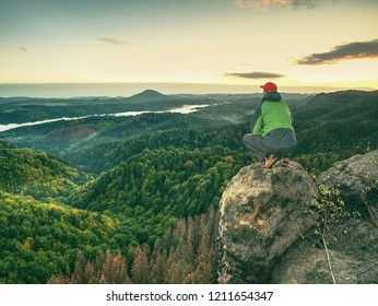 Man walking on the edge of a cliff at summit. Hrensko range,  Czech Republic 21st of Seprtember 2018.  Climber enjoying beautiful nature view at sunset after challenging climb