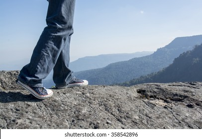 Man walking on edge of a cliff mountain top , travel concept