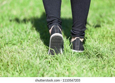Man walking on grass in sports shoes, close-up rear view