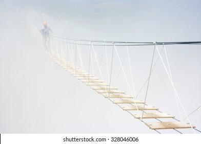 Man walking on hanging bridge in fog.