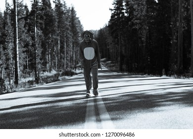 Man walking on the highway in elephant costume black and white