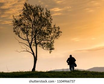 Man walking on a hill at sunrise