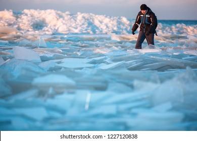 Man walking on icy beach along the Baltic sea in Latvia, Jurmala