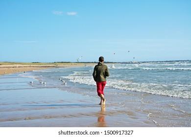 man walking on the ocean shore