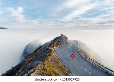 Man walking on the Portuguese flag road. Mountain serpentine road walking along the top of the ridge above the clouds. Madeira