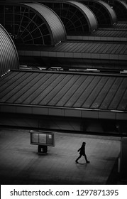 A man walking on a railway station under the gloomy roof construction.