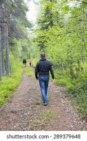 A man walking on a road in the deep forest in the summer. Other people is walking ahead of him.