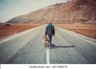 man walking on the road with his dog in the mountains