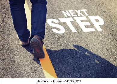"""Man walking on the road with inspiration quotes """"NEXT STEPS"""""""