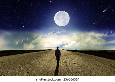 Man walking on the road at night in the moonlight