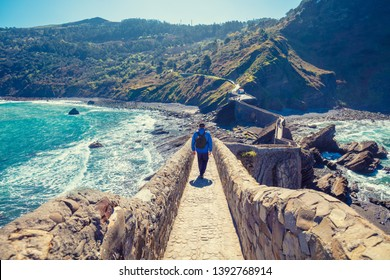A man walking on rocky wall to island Gastelugatxe. Biscay, Basque country, Spain, Europe