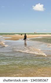 Man walking on shallow waters at Sao Paulo beach - Itamaraca island, Brazil
