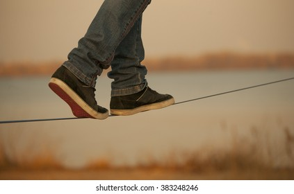 man walking on Slackline on the background of the river. Visible only  legs