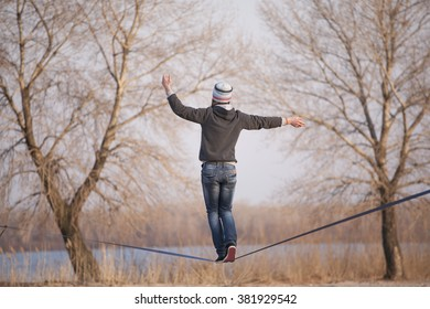 Man walking on slackline with river view in the park