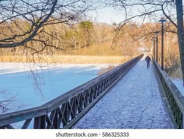 A man walking on a slippery footbridge over a frozen lake