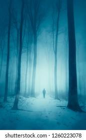 man walking on snowy road in forest on winter night