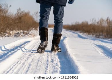 Man walking on a snowy road.