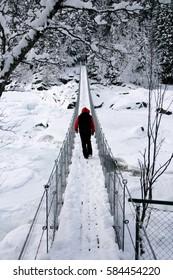 Man walking on a snowy suspension bridge