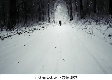 man walking on snowy winter road in winter