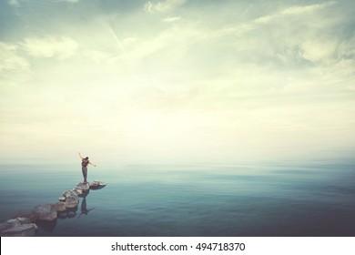 Man walking on stones finding balance over water