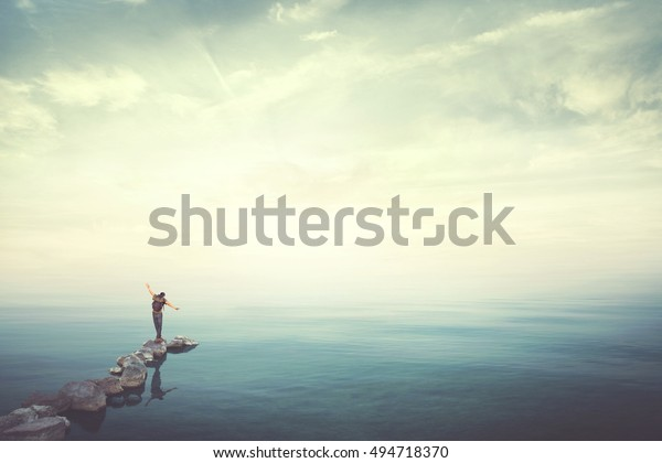 Man walking on stones finding balance over water