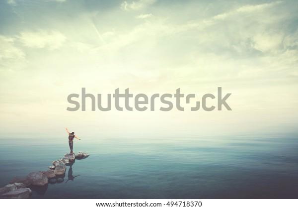 Hombre caminando sobre piedras encontrando equilibrio sobre el agua