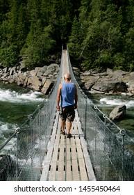 Man walking on a suspension bridge in summer
