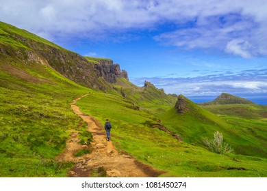 A man walking on the trail at the Quiraing, Isle of Skye, Scotland.