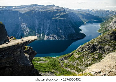 A man walking on the Trolltunga rock with a blue lake 700 meters lower and interesting sky with few clouds