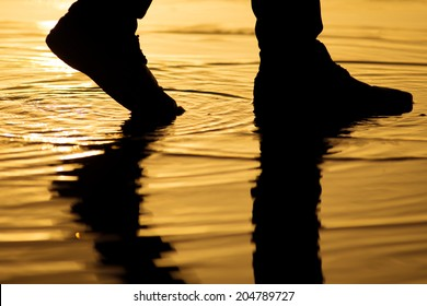 Man walking on the water surface with silhouette legs reflection.