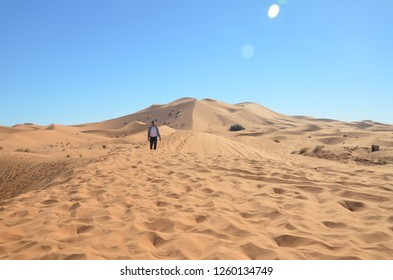 A man walking on the West Sahara Desert at Merzouga. Merzouga is a small Moroccan town in the Sahara Desert, near the Algerian border.