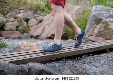 Man walking on a wooden bridge crossing water stream on summer day