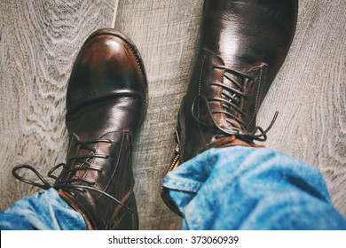 man walking on a wooden floor in jeans and high boots, point of view perspective. Vintage style, grunge style