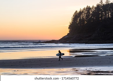 Man walking out of the cold waters of the Oregon coast with his surf board as the sun adds an orange glow across the horizon