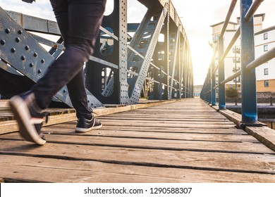 Man walking over a bridge at sunset. Close up view on legs of one person walking on wooden sidewalk across a bridge.