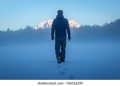 Man walking over frozen lake on a cold winter day
