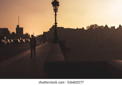 Man walking over the Putney Bridge during beautiful sunset. Golden hour