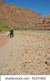A man walking with paddleboard on rocky beach in Desolation Canyon UT