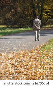 A man walking the park fulled with autumn leaves.