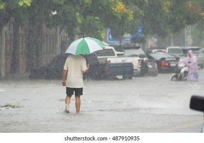 Man walking in the rain on flooded road