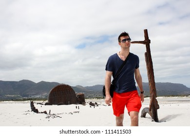 Man walking at Shipwreck Kakapo at the beach of kommetjie with upcoming storm in the background