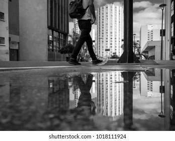 Man walking in the sidewalk in the city and his reflection on a water puddle. Black and white artistic version