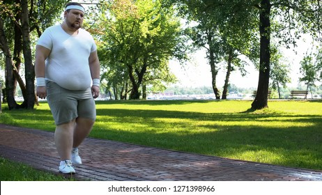 Man walking slowly, exhausted after running, cardio training for weight loss