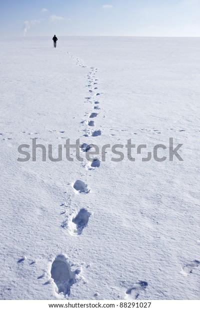 Man walking i snow making foot prints